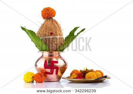 Copper Kalash With Coconut And Mango Leaf And Pooja Thali With Diya, Kumkum And Sweets With Floral D