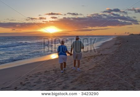 Couple Walking Into A Sunset