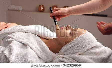 Beautiful Woman With Facial Mask At Beauty Salon.applying Facial Mask At Woman Face At Beauty Salon.
