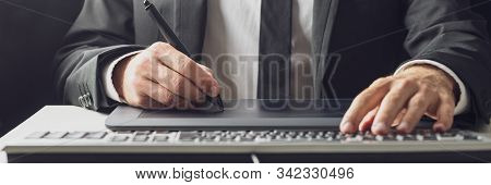Wide View Image Of Businessman Or Graphic Designer Using A Stylus Pen And Tablet While Typing On His