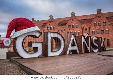 Gdansk, Poland - December 15, 2019: Gdansk city sign at the Philharmonic of Gdansk with christmas hat, Poland