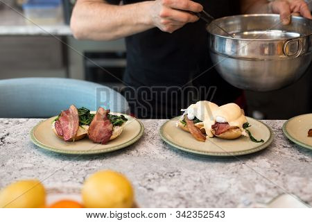 Eggs Benedict With Crisp Bacon And Spinach Being Topped With Hollandaise Sauce For Morning Brunch.