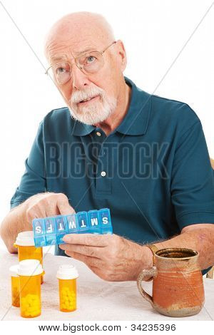 Confused senior man can't remember whether or not he took his pills.  Could be early sign of Alzheimer's Disease or dementia.