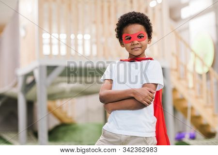 Cute African little boy in white casualwear and red mantle of superman looking at you while playing in kindergarten