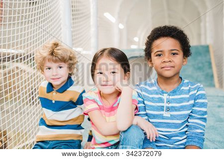 Cute restful boys and girl of Asian, Caucasian and African ethnicities spending time on play area at leisure center