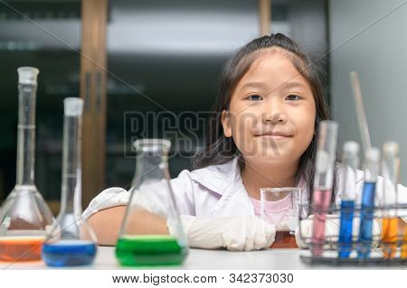 Happy Little Girl Wearing Lab Coat Making Experiment In Chemical Laboratory, Ecucation And Science C