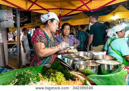 Krabi Town, Thailand - November 23 2019: Young Thai Woman Prepares Delicious Thai Food At Krabi Week