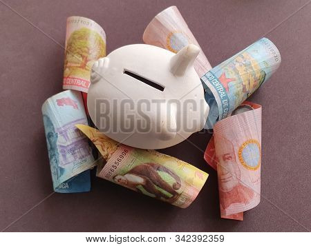 White Piggy Bank And Costa Rican Banknotes Of Different Denominations