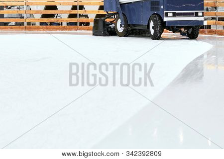 Ice resurfacing machine , Ice resurfacer, resurfacing the ice rink in the central park of the town. poster