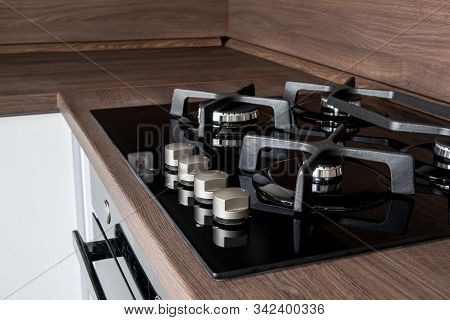 A Modern Gas Cooker With Ceramic Hob, Electric Oven And A Dark Brown Wooden Kitchen Ready For Cookin