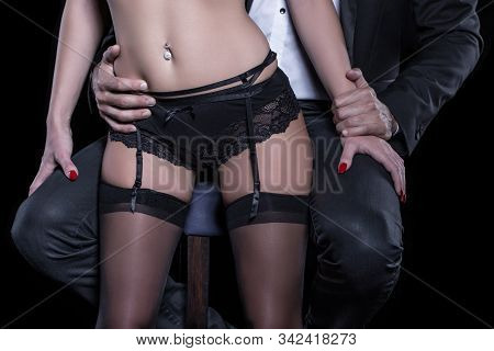 Man On Stool Holding Lover In Underwear Body Closeup, Isolated On Black