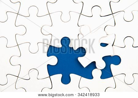 White Puzzle Over Blue Backround With Missing Pieces. Incomplete Elements, Solution Search Concept.