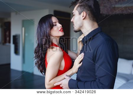 Tempting Sexy Woman In Red Seducing Younger Man Indoors