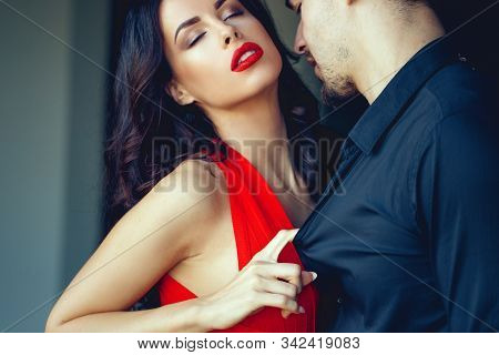 Tempting Milf Woman In Red Dress And Lips Seducing Young Lover Indoors
