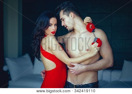 Tempting Milf Woman In Red Seducing Sexy Younger Man Indoors, Looking Into Camera