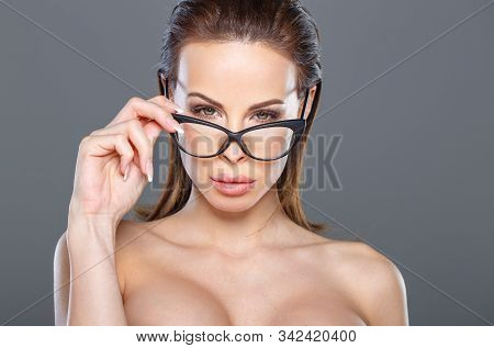 Sexy Young Tempting Brunette Woman Looking While Taking Off Eyeglasses