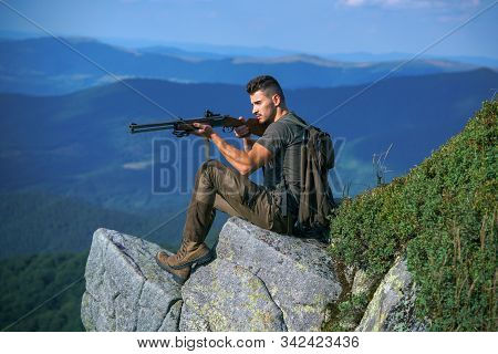 Hunting Licenses. Illegal Hunting Poacher In The Forest. Handsome Hunter Man Holding Gun And Walking