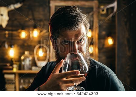Man With Beard In Black With Glass Of Beverage. Bearded Man Holds Glass Of Brandy. Bearded Hipster D