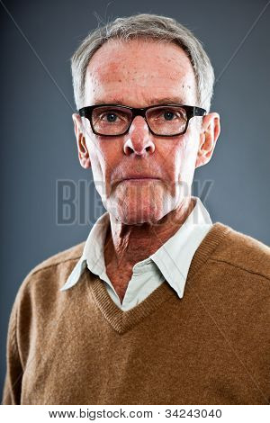 Expressive good looking senior man wearing glasses against grey wall. Well dressed. Studio shot. poster