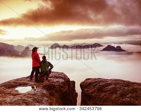 Lovely Heterosexual Couple Looking At Far Sunrise In Heavy Clouds. The Dark Night In Foggy Mountains