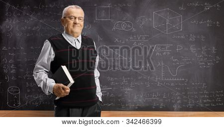 Elderly professor with a book standing in front of a blackboard with math formulas