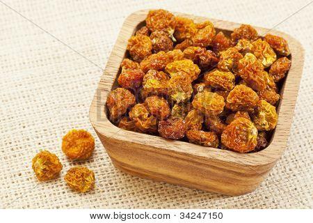dried goldenberries (physalis peruviana,) , superfruit from Peru rich in antioxidnats, vitamin A, bioflavonoids, and dietary fiber, a wooden bowl