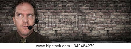 Unfriendly Confused Businessman with Frowning Face Wearing Phone Headset In Office with Brick Background Banner.