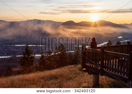 Girl Standing On A Lookout And Looking At A Beautiful View Of A Canadian City, Kamloops, During A Co