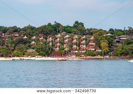 Houses Built On A Hill In Phi Phi Island. Longtail Boats And Andaman Sea In The Foreground.
