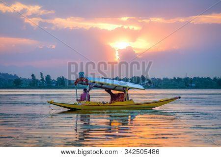 A Wooden Boat (shikara) In Dal Lake, Srinagar, Kashmir On A Beautiful Sunset Evening