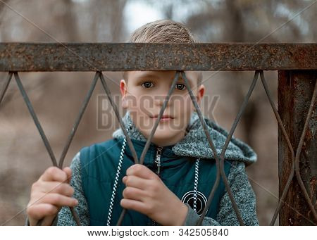 Close-up Portrait Of A Cute Teen Boy Standing Behind A Metal Fence.