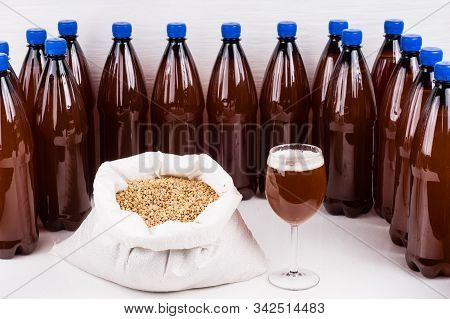 Plastic Bottles And Glass Of Craft Beer With  Bag Of Light Malt  On A Wooden Table On White Backgrou
