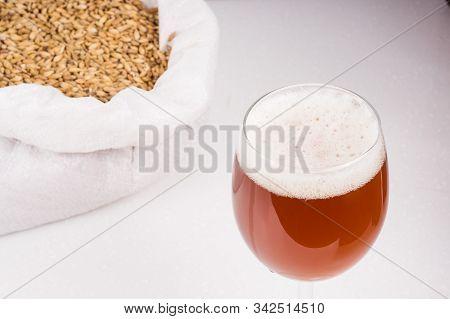 Glass Of Homemade Beer And Bag Of Light Malt On The Background.  Ale Or Lager From Pilsner Malt