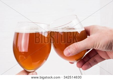 Two Hands Holding A Glass Of Homemade Craft Beer On White Background.  Ale Or Lager From Pilsner Mal