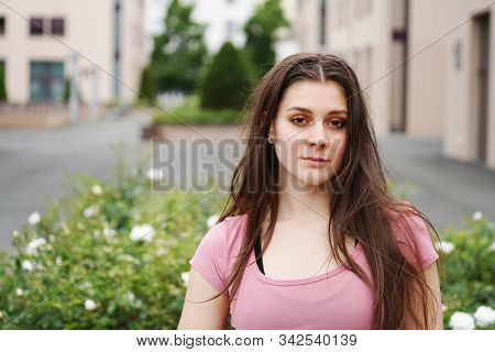 Street Portrait Of A Serious Young Woman With Long Brunette Hair Outdoor. Beautiful Young Female In