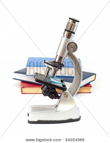 Microscope, books isolated on white