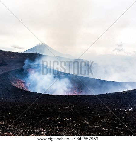 Crater Of Erupting Volcano. Red Hot Lava Flies From The Vent Of The Volcano