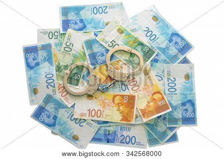 Handcuffs On Israeli Money Isolated On A White Background. The New Israeli Money Bills (banknotes) O