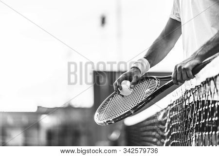 Black & White Image Of Young Man Playing Tennis Outdoors. Close Up Of Man Hands Holding Tennis Racke