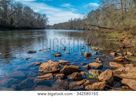 A Bright Sunny Day At The River With Rocks And Boulders In The Foreground And The Woodlands In The B