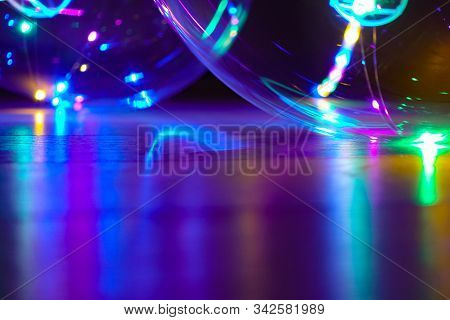 Colored Lights Reflect Off A Shiny Surface At Night. Bokeh Abstract Holiday Background