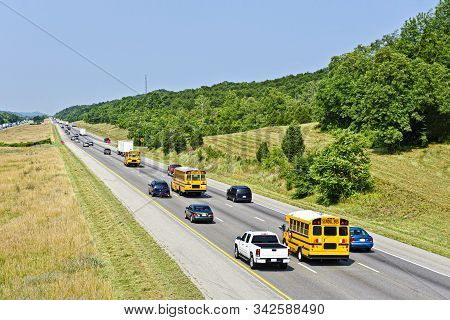 Horizontal Shot Of Yellow School Buses On An Interstate Highway.