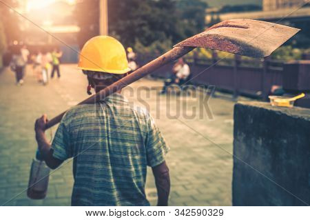 Chinese Worker Carrying His Shovel On His Arm And Going Home After Finishing His Work Shift