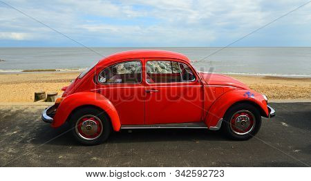 Felixstowe, Suffolk, England - May 05, 2019:  Classic Red  Vw Beetle Parked On Seafront Promenade Wi
