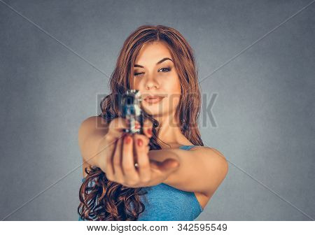 Beautiful Woman Aiming To Shoot With A Gun, One Eye Closed Isolated On Gray Background. Brunette Hol