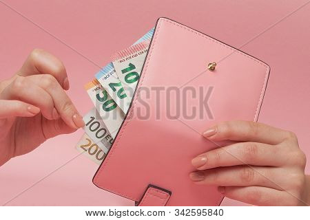 Pink Purse And Euro Banknotes In Female Hands On Pink Background. Business Concept And Instagram