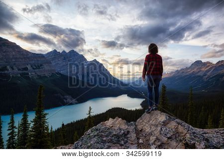 Adventurous Girl On The Edge Of A Cliff Overlooking The Beautiful Canadian Rockies And Peyto Lake Du