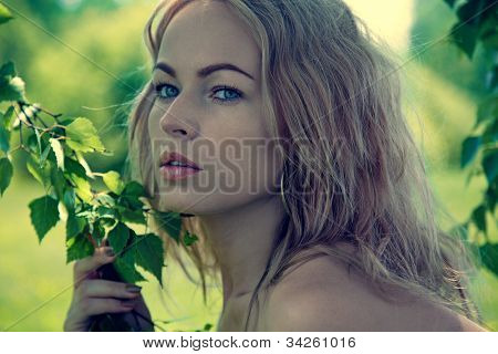 Fashion portrait of young beautiful blond woman in forest