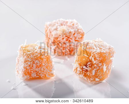 Turkish Delight Fruit-flavoured Rahat Lokum Three  Pieces With Coconut Crumbs Close-up On White Back