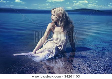 Young sexy blond woman in the blue water in wet white dress